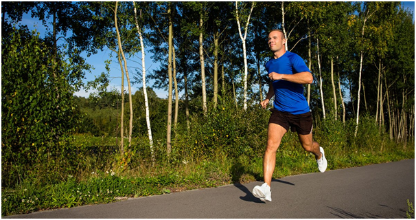 Man in a blue running shirt and black running shorts running on a trail
